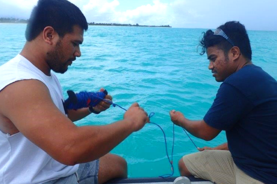 two people gathering water samples on boat